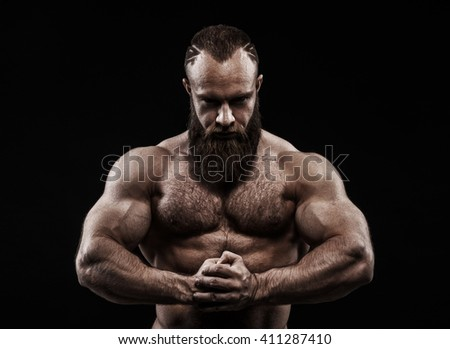 Strong man with perfect abs, shoulders, biceps, triceps and chest. Bodybuilder topless over black background. #411287410