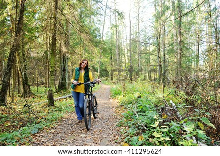 Young woman on bike standing on road and looking to somewhere #411295624