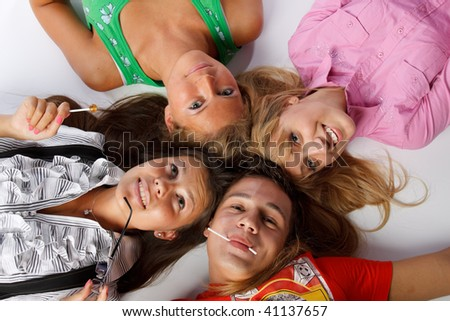 Young happy people lay with sugar candies on a white background. #41137657