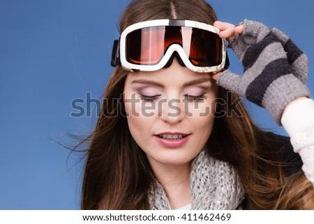 Woman skier girl wearing warm clothing ski googles portrait. Winter sport activity. Beautiful sportswoman on blue studio shot #411462469