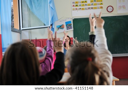 happy young teacher woman at elementary school teaching and giving lessons to group of young smart children #41151148