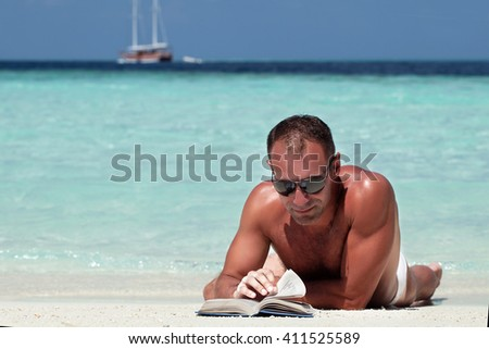 handsome man reading book at the white sand beach #411525589