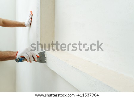 Decorative plaster coating. Man does ragged texture on the wall using a spatula. #411537904