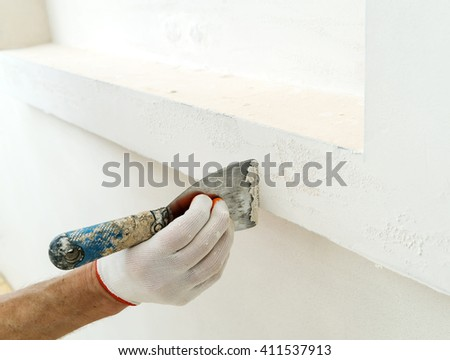 Decorative plaster coating. Man does ragged texture on the wall using a spatula. #411537913