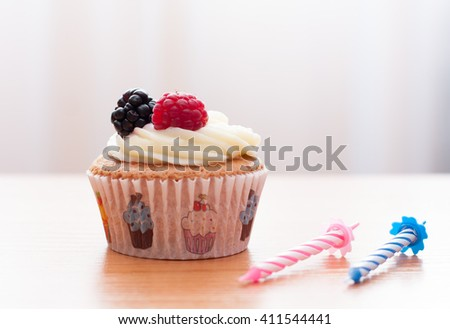 Birthday homemade cupcake with fresh raspberry, blackberry and cream  topping on wooden desk and candles on it #411544441