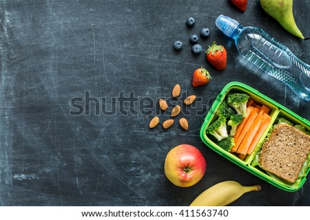 School lunch box with sandwich, vegetables, water, almonds and fruits on black chalkboard. Healthy eating habits concept - background layout with free text space. Flat lay composition (top view). #411563740