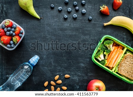 School lunch box with sandwich, vegetables, water, almonds and fruits on black chalkboard. Healthy eating habits concept - background layout with free text space. Flat lay composition (top view). #411563779