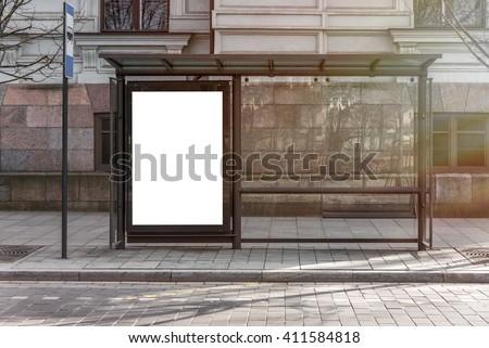Blank white mockup of bus stop vertical billboard in empty street Royalty-Free Stock Photo #411584818