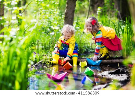 Children play with colorful paper boats in a small river on a sunny spring day. Kids playing exploring the nature. Brother and sister having fun at a forest stream. Boy and girl with toy boat and ship #411586309