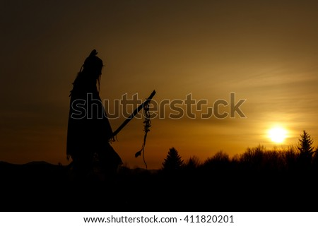 silhouette of native american shaman with pikestaff on background of sunset beautiful in mountains #411820201