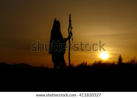 silhouette of native american shaman with pikestaff on background of sunset beautiful in mountains #411820327