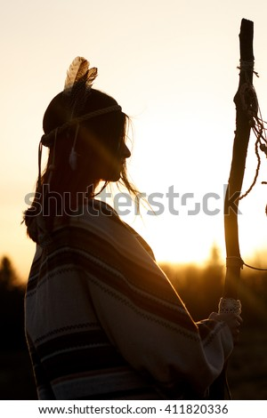 native american woman  shaman with pikestaff on background of sunset beautiful in mountains