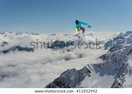 Snowboard rider jumping on mountains. Extreme snowboard freeride sport. #411832942