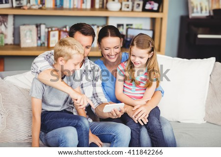 Happy family using mobile phone while sitting on sofa at home #411842266