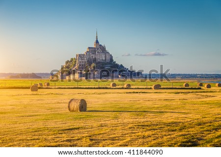 Beautiful view of famous historic Le Mont Saint-Michel tidal island in beautiful golden evening light at sunset in summer with hay bales on empty fields, Normandy, northern France #411844090