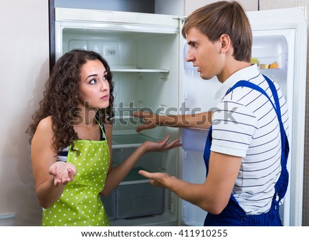 Tired handyman cannot repair refrigerator at the kitchen of young female client  #411910255