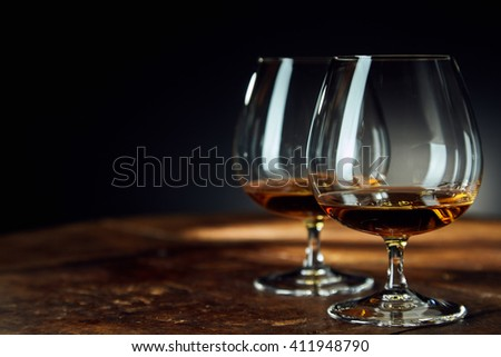 Close up of two glass goblets with alcohol resting on a wooden table against a dark background #411948790