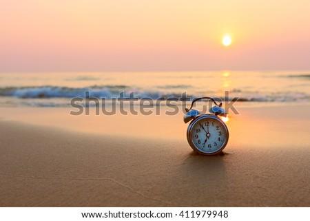 Alarm clock vintage with sunrise on beach