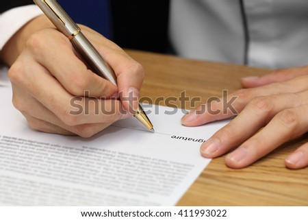 close-up on a businessman hand signing a contract paper #411993022