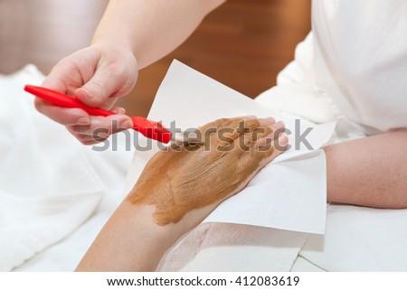 Therapist applying nourishing mask on woman's hand #412083619