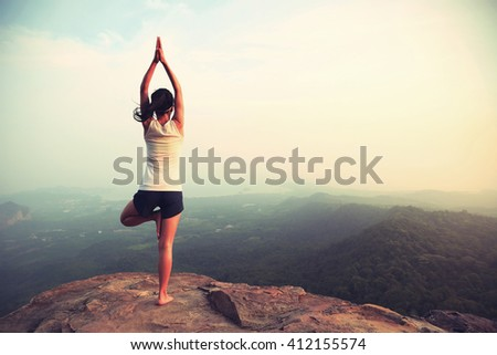 young fitness woman practice yoga at mountain peak cliff #412155574