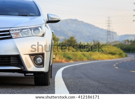 Close up front of new silver car parking on the asphalt road Royalty-Free Stock Photo #412186171