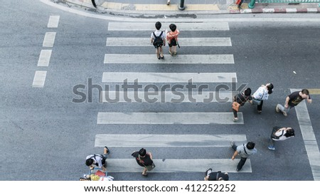People and couple are walking across the crosswalk on top view (aerial photo) #412252252