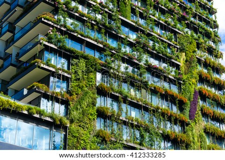 Green skyscraper building with plants growing on the facade. Ecology and green living in city, urban environment concept. Park in the sky, One central park building, Sydney, Australia #412333285