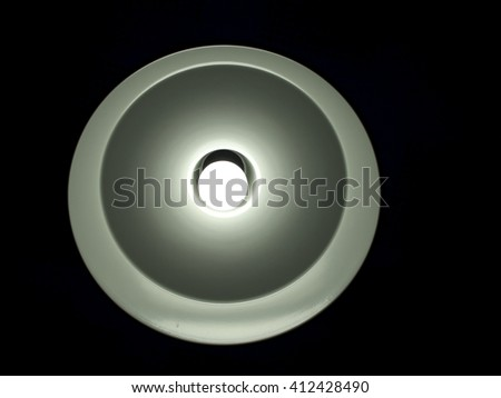 Bright round shaped lamp isolated on black background. Interior design. #412428490