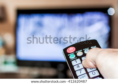 Hand hold the remote control to change channels on Television #412620487