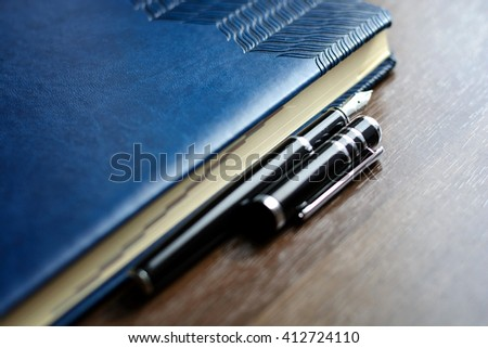 Business accessories on desktop: notebook, diary, fountain pen. Macro with blur and soft focus. With vignette.  #412724110