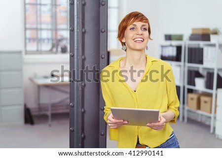 Office worker with red hair and wearing yellow shirt smiles while leaning against beam #412990141