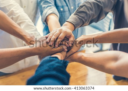 business people making pile of hands , soft focus, vintage tone  Royalty-Free Stock Photo #413063374