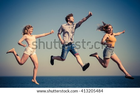 Carefree young friends people jumping by sea ocean water. Happy women and man having fun. Summer happiness and freedom. #413205484