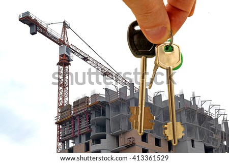 The keys to the apartment in hand on the background of houses #413361529