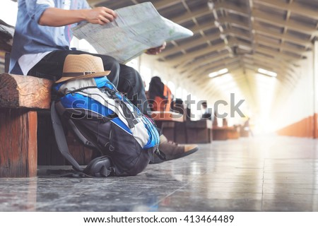 Backpack and hat at the train station with a traveler. Travel concept. Royalty-Free Stock Photo #413464489