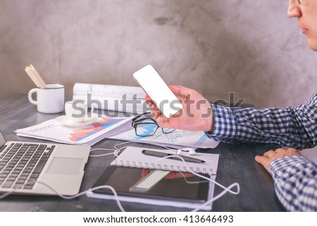 Sideview of male with blank white smartphone in hand sitting at office desk with business report and electronic devices. Mock up #413646493