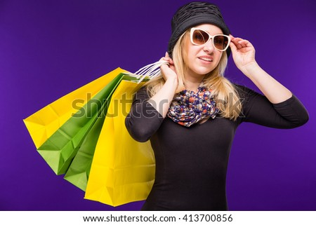 woman in glasses with shopping bags on a blue background #413700856