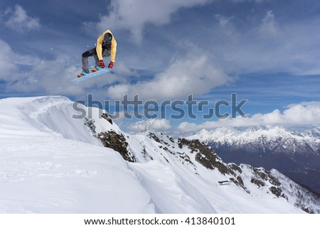 Snowboard rider jumping on mountains. Extreme snowboard freeride sport. #413840101