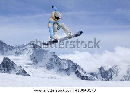 Snowboard rider jumping on mountains. Extreme snowboard freeride sport. #413840173