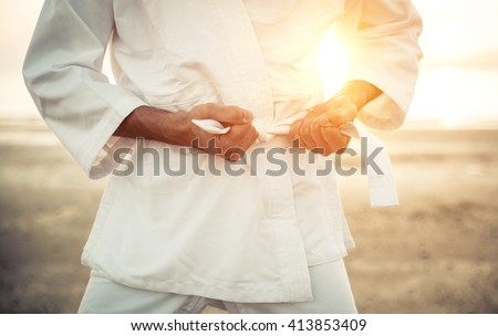 Karate fighter tying his kimono belt up, concept about martial arts Royalty-Free Stock Photo #413853409
