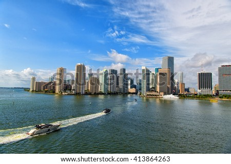 Aerial view of Miami skyscrapers with blue cloudy sky, boat sailing next to Miami downtown #413864263