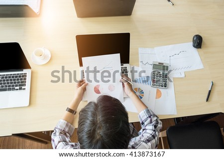 Business woman working at the office. analysis document using laptop and calculator #413873167