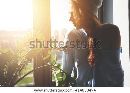Pretty hipster girl with bare shoulder sitting on the windowsill waiting for her friends to go out for a walk on sunny summer day with sunbeams and lens flare, enjoying urban view through the window #414050494