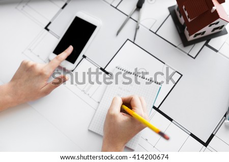 business, architecture, building, construction and people concept - close up of architect hand with living house blueprint and smarphone writing to notebook #414200674