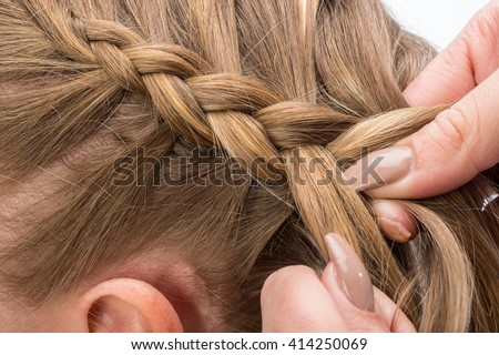 Hairdresser braids long straight hair isolated on white background. #414250069