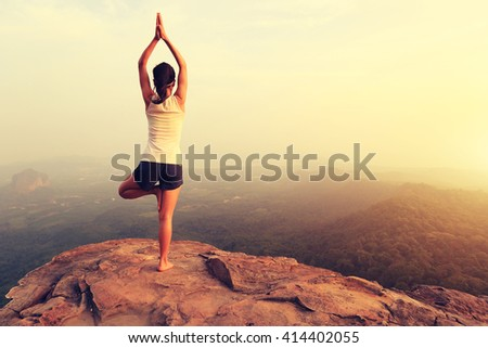 young fitness woman practice yoga at mountain peak cliff #414402055