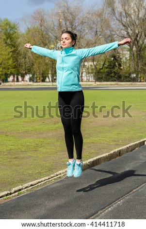 girl with a sports body is doing exercises outdoors in spring #414411718