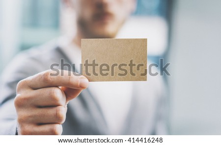 Closeup photo man wearing casual shirt and showing blank craft business card. Blurred background. Ready for private information. Horizontal mockup