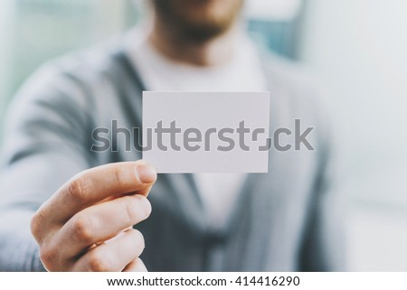 Closeup photo man wearing casual shirt and showing blank white business card. Blurred background. Ready for private information. Horizontal mockup #414416290